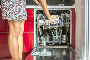 Woman Emptying Open Dishwasher